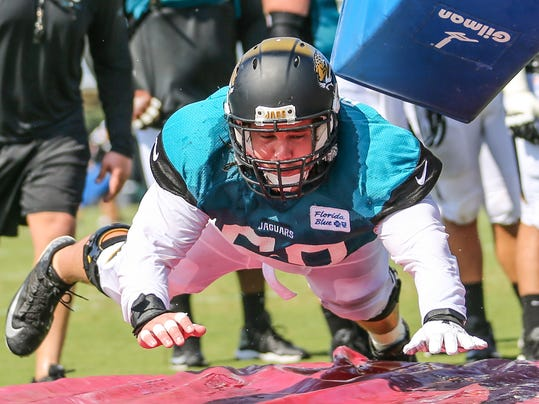 Jacksonville Jaguars center Mike Brewster (60) dives through a tackling dummy during NFL football training camp in Jacksonville, Fla.,Wednesday, July 30, 2014. (AP Photo/Gary McCullough)