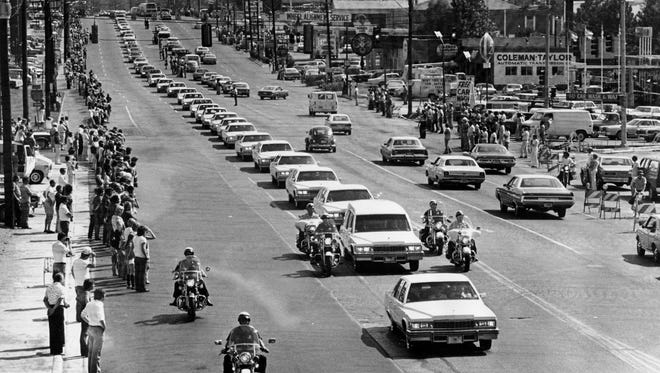 A string of white vehicles follow the hearse carrying the body of Elvis on the way to Forest Hills Cemetery in Memphis, Tenn., Aug. 19, 1977.