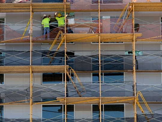 A construction crew attaches sections of the outside