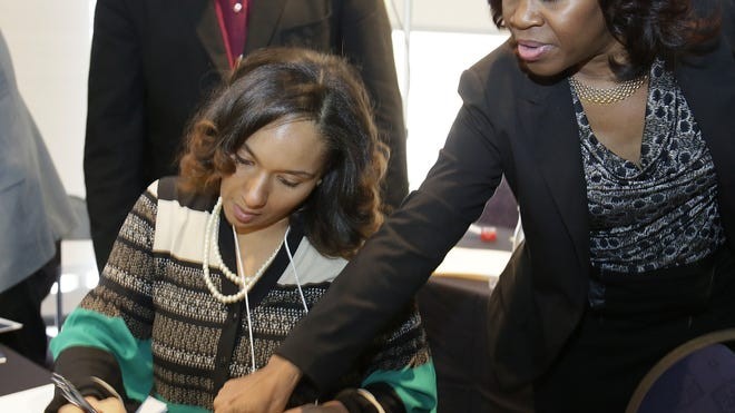 Detroit City Council member Mary Sheffield, left, gets a hand from Detroit City Clerk Janice Winfrey as Sheffield signs her oath of office papers Dec. 11, 2013.