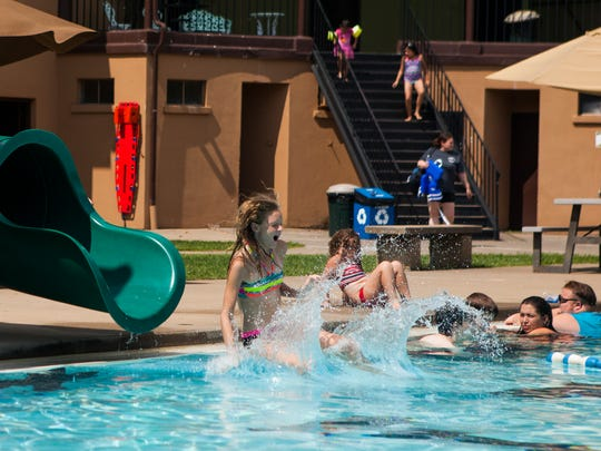 Briana Marsh, 9, splashes out of the water slide at the Gypsy Hill Park pool on Saturday, Aug. 15, 2015.