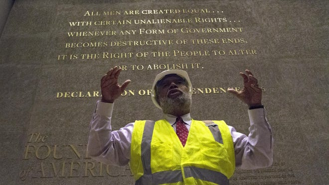 In this photo taken July 18, 2016, Museum Director Lonnie Bunch stands in front of one of the engraved walls of the Smithsonian's National Museum of African American History and Culture in Washington, during a media preview tour. The museum's grand opening will be on Sept. 24.
