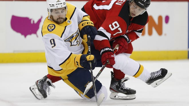 Devils' Nikita Gusev (97) and Predators' Filip Forsberg go after the puck as Forsberg falls to the ice during the second period.