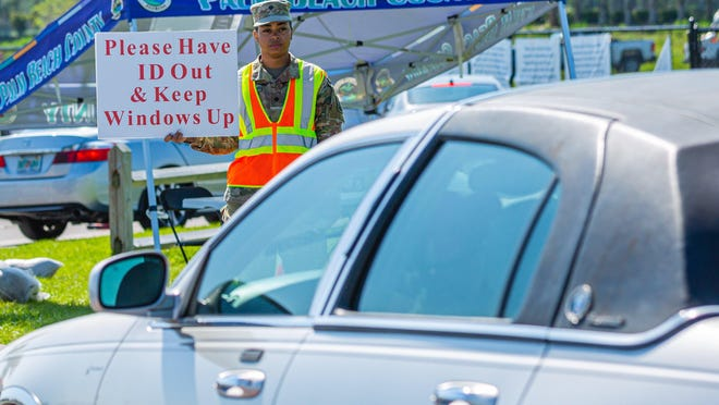 A National Guardsman directs drivers to have their identification ready and to keep their windows up on April 27 at the coronavirus testing site at the FITTEAM Ballpark of the Palm Beaches in West Palm Beach.