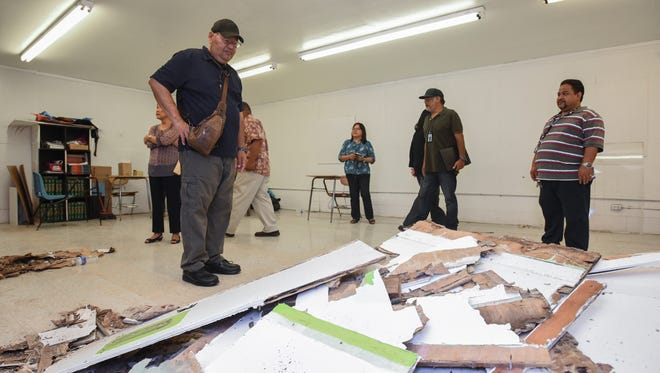 In this April 18 file photo, Guam Education Board member James Lujan looks at a pile of deteriorating wall-paneling material on the floor of a temporary classroom at Simon Sanchez High School.