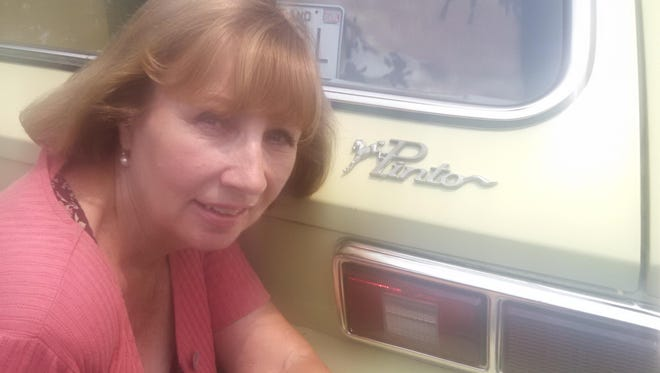 Christine Smith of Salisbury kneels next to her 1977 heirloom Ford Pinto, which her mother purchased to observe the death of Elvis Presley.