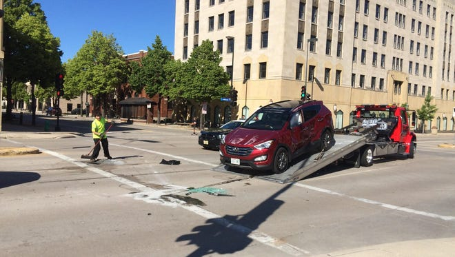 Authorities clean up after a rollover crash Tuesday at East Walnut and Adams streets in downtown Green Bay.