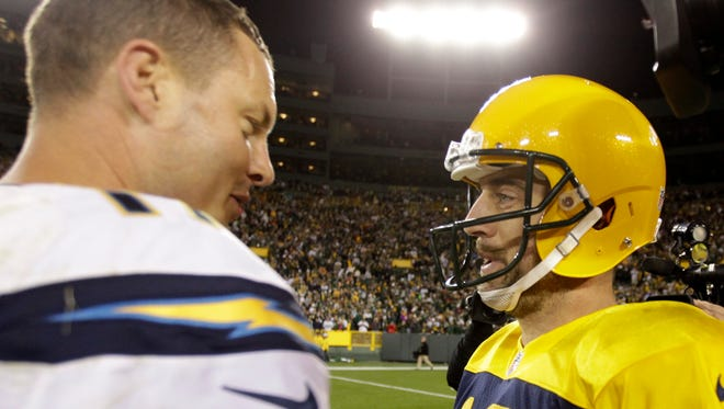 Green Bay Packers quarterback Aaron Rodgers and San Diego Chargers quarterback Philip Rivers meet on the field after their Week 6 matchup in 2015.