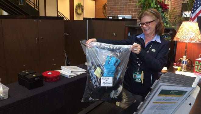 Carolyn Zeise holds up a bag of found items at Lambeau Field. Items are tagged and logged in so they can be returned to owners when they call about them.