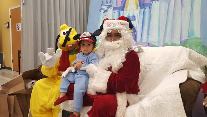 """Keanu Hernandez, 18 months, visits Santa Claus and Pluto and makes the sign for """"love,"""" Saturday, Dec. 10, 2016, during the Deaf and Hard of Hearing Center of Corpus Christi's Signing Santa event."""