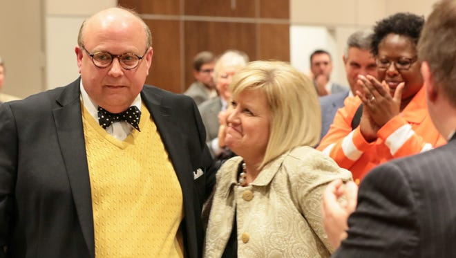 Evans Whitaker, left, is hugged by his wife Diane and applauded by many others on Thursday during the United Way of Anderson County's  Communitarian Award dinner  at Anderson University.