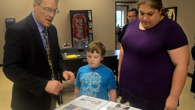 Steve Coffman, editor of The Jackson Sun, presents two commemorative front pages of the newspaper to Ashley Blankenship, her son Chase and daughter Bailey (not pictured). The pages honor Blankenship's husband, Madison County Firefighter Chris Blankenship, who died last month in the line of duty.