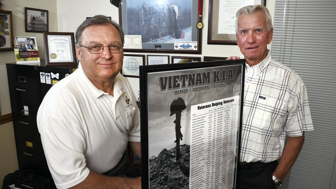 Vietnam Veterans Kenneth Schulte and Dennis Kurtz talk Thursday, July 30 about bringing The Wall That Heals Vietnam Memorial replica exhibit to the Benton County Fair. They are holding a list of names of veterans that were killed in action during the war from Benton, Stearns and Sherburne counties.