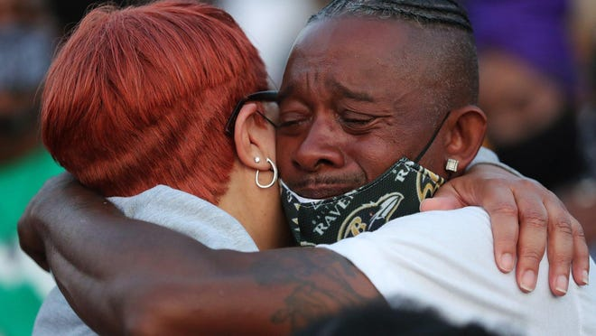 Na'Kia Crawford's loved ones comfort each other before a candlelight vigil Monday in Akron.