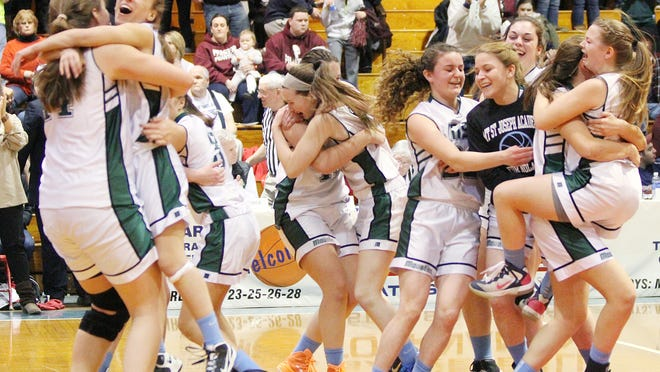 Members of the Mount St. Joseph's girls basketball team celebrate its 35-29 win over Proctor in the Division IV high school state championship game at Barre Auditorium on Saturday.
