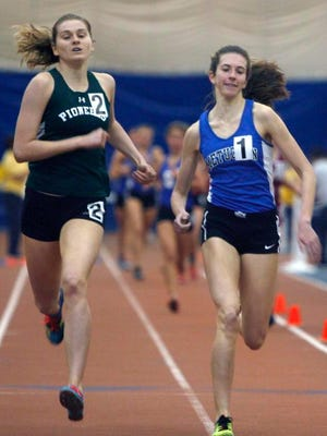Jillian Turner of New Provience (left) and Rachel Suss of Metuchen compete in the 1600 during the Central Groups I and IV indoor track sectional championships on Friday at the Bennett Center in Toms River.