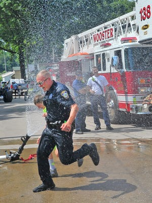 K-9 Officer Josh Timko and Connor Rotolo take a run through the water sprinkler at the third annual Five-O Community Cookout in 2018. The cookout is one of a number of events the police department participates in annually. Many events are in limbo depending on how quickly restrictions on gatherings are lifted.