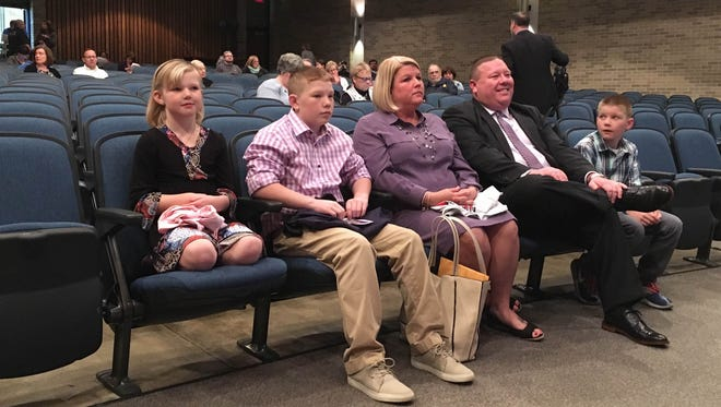 Christopher Walker sits with his family at the Muncie Community Schools board meeting March 29. The board hired Walker as principal of Central High School for next school year.