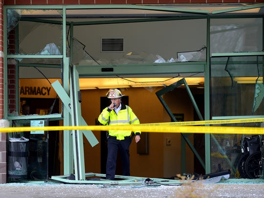 A fire official walks out of the damaged entrance to