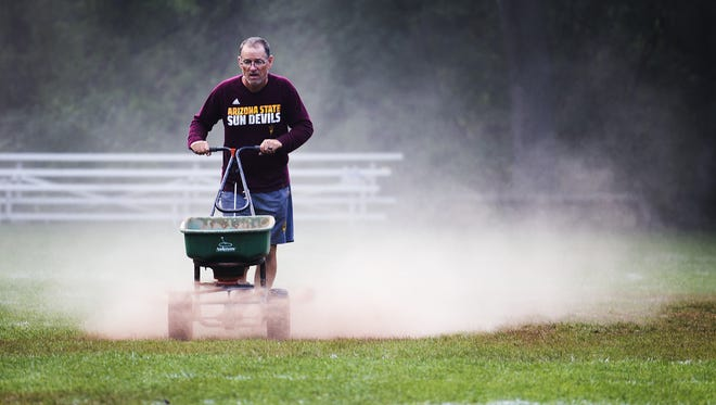 A worker lays down drying agent on the field at Camp Tontozona early Saturday, August 5, 2017, in anticipation of the final day of Arizona State University football practice.  Overnight rain soaked the field.