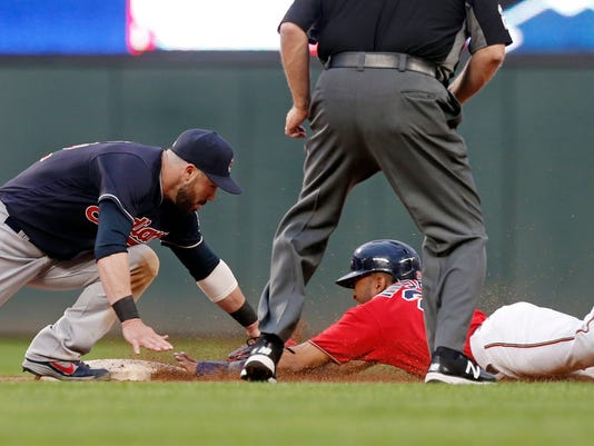 Minnesota Twins' Eddie Rosario, bottom right, is tagged out by Cleveland Indians second baseman Jason Kipnis as he attempted to take the base after Brian Dozier flew out in the fourth inning of a baseball game Friday, June 16, 2017, in Minneapolis. (AP Photo/Jim Mone)