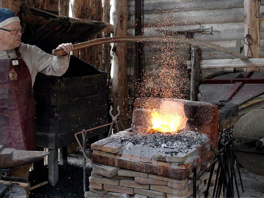 Blacksmith Pete Santoro pumps the bellows at Mansker's Station Heritage Days in Goodlettsville on April 7, 2018.