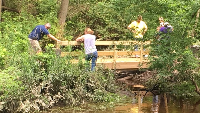 Volunteers work on one of the 12 foot bridges installed this spring and summer on the newly opened trail along Fall Creek in Freeville's Genung Nature Preserve.