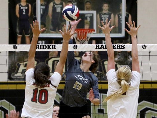 Rider's Meredith Fisher spikes the ball past Holliday's