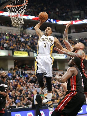 Pacers George Hill flies to the hoop around Miami's Luol Deng and Chris Andersen for a slam dunk in the first half of the game at Bankers Life Fieldhouse on Wednesday, Dec. 31, 2014.