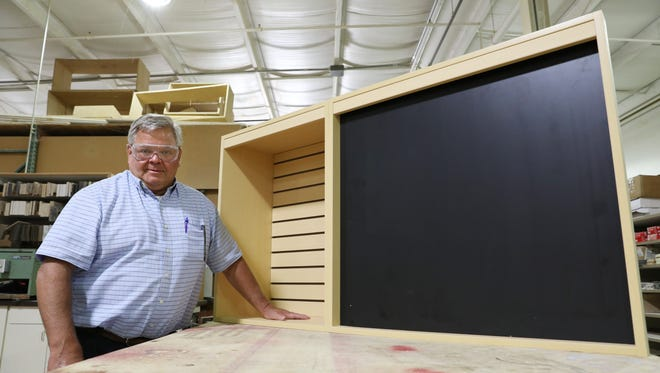 President Joe Nash stands next to one of the custom cabinets being constructed at Zanesville Fabricators on Chandlersville Road.