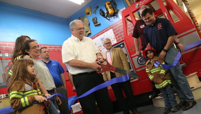Neil Hamilton of Hamilton Insurance cuts the ribbon for the new fire truck exhibit at the Little Buckeye Children's Museum on Friday evening.