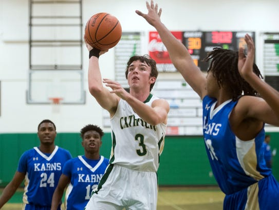 Catholic's Ryan MacDonald attempts to score while defended