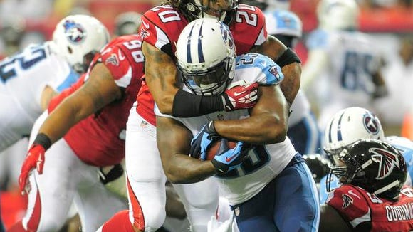 Titans running back Shonn Greene is stopped by Falcons free safety Dwight Lowery during the second quarter at the Georgia Dome on Saturday.