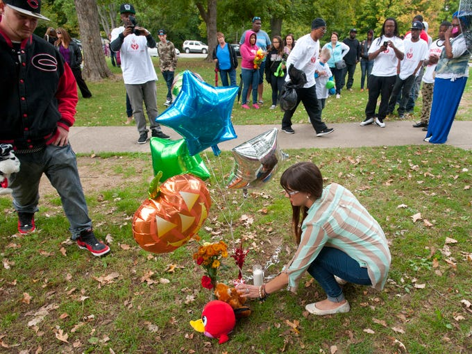 "Monica Lun, who's foster son and stepson are brothers of Ray Etheridge, lay a toy at a makeshift memorial to him during a ""Let the Kids Grow reflection ceremony""  at Hogan's Fountain in Cherokee Park near the area where Etheridge was murdered. . 05 October 2014"