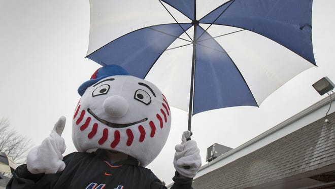 The mascot for the Mets carries an umbrella as he prepares to march in the Toms River East Little League  opening-day parade in 2014.