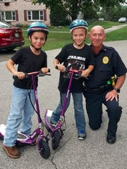 "Nine-year-olds Draycen and Dawsen Wise stand next to Southwestern Regional Police Officer Stu Harrison after he handed out their ""positive tickets."""