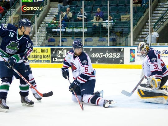 Florida Everblades forward Mike Aviani, left, slips a goal past South Carolina goalie Adam Morrison in the first period on Wednesday, Jan. 28, 2015, at Germain Arena in Estero.