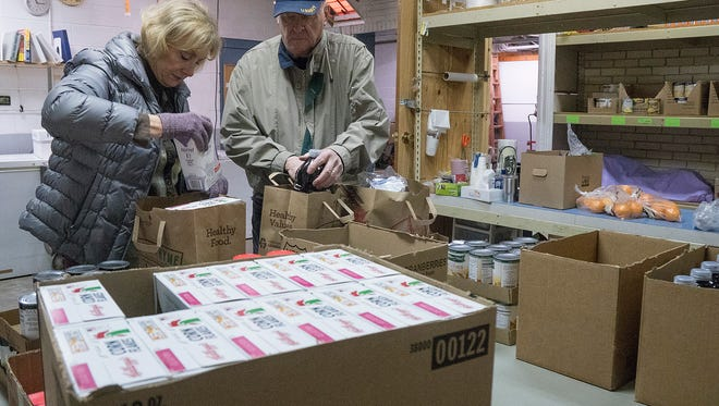 Long-time volunteers Carol and Steve Lawrence package items from the food pantry for clients. They are from Northville Twp.