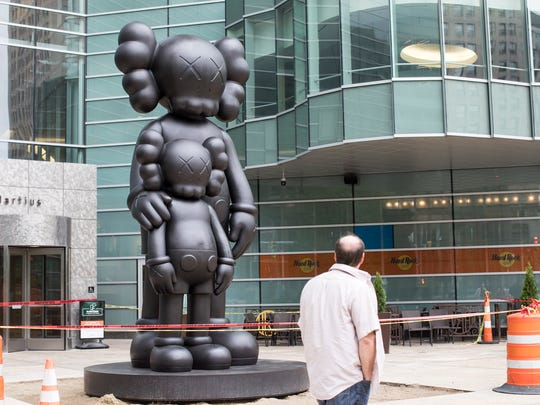 "A pedestrian passes by the 17-foot statue titled ""Waiting"" by  artist Kaws at the main entrance to One Campus Martius in Detroit, Sunday, May 20, 2018."
