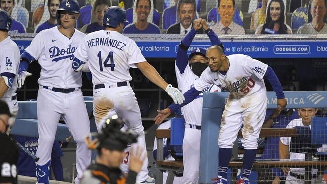 Los Angeles Dodgers' Kiké Hernández, second from left, is congratulated by Mookie Betts, right, Joc Pederson, left, and manager Dave Roberts after hitting a two-run home run during the eighth inning of an opening day baseball game on Thursday, July 23, 2020, in Los Angeles.