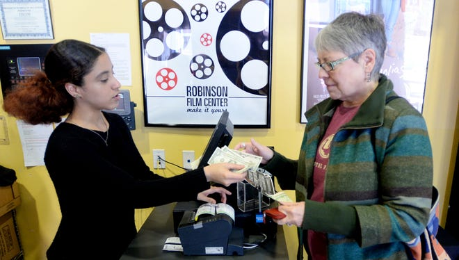 Ellen Stetson buys tickets from Arianne Woodfork, left, at the Robinson Film Center.