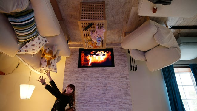 A visitor poses inside an upside-down house created by a group of Taiwanese architects at the Huashan Creative Park in Taipei, Taiwan, Tuesday, Feb. 23, 2016. With a build price of $600,000 and over 300 square meters (3,230 square feet) of floor space filled with real home furnishings, the upside-down house will continue to be on display to visitors until July 22.