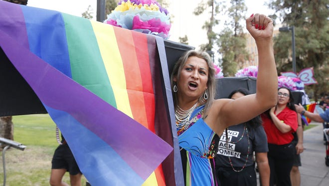 Karyna Jaramillo, 46, of Phoenix, carries an empty coffin during a LGBTQ and people of color funeral procession in downtown Phoenix to honor those that were killed by the Phoenix Police Department.