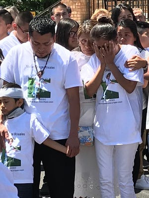 The family of Matías Ortega-Rosales looks on as he's leaded into a hearse outside the church on Thursday.