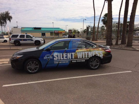A Silent Witness car is parked near the light-rail