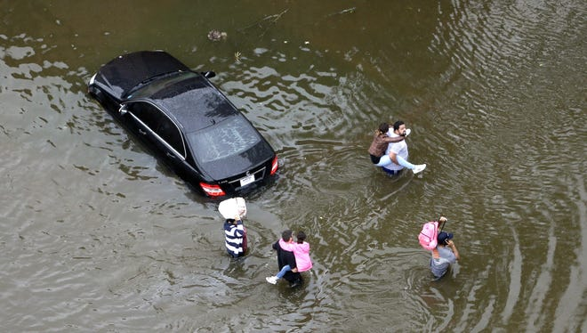 Residents wade through floodwaters as they evacuate their homes near the Addicks Reservoir as floodwaters from Tropical Storm Harvey rise in Houston.