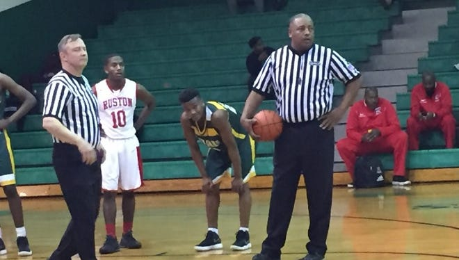 Game officials await a substitute after Ruston big man Ray Parker left the game with an injury.