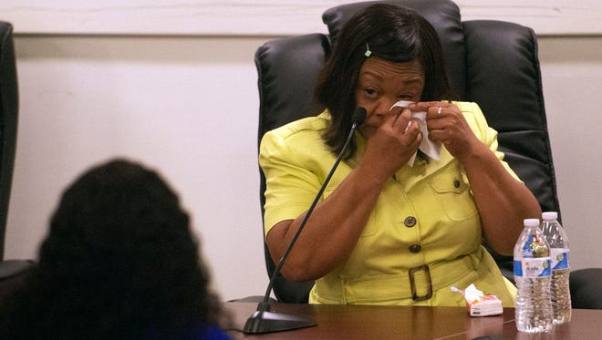 Sandra Harrison wipes her eyes after testifying during a human relations commission hearing on Friday. Harrison was one of five black women who were playing golf in April when police were called by the Grandview Golf Course for alleged slow play.