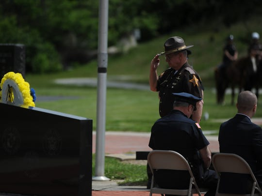Wayne County Sheriff's Department Major Mike Frame salutes after placing a flower during the May 20 Peace Officers Memorial Service at Veterans Memorial Park. Frame previously served in the Air Force.
