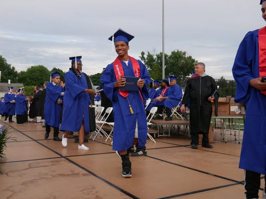 Erik Ramos smiles after getting his diploma during